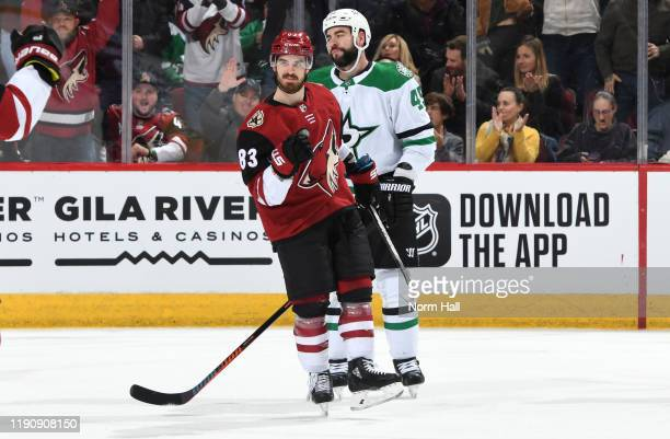 Conor Garland of the Arizona Coyotes pumps his fist after scoring a goal as Roman Polak of the Dallas Stars reacts during the first period of the NHL...