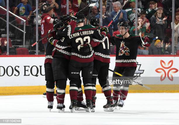 Conor Garland of the Arizona Coyotes skates in to celebrate with teammates Jakob Chychrun Oliver EkmanLarsson and Alex Galchenyuk after Galchenyuk's...
