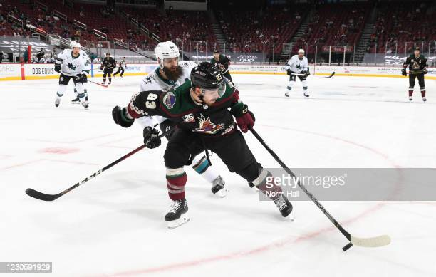 Conor Garland of the Arizona Coyotes skates with the puck as Brent Burns of the San Jose Sharks defends during the second period of the NHL hockey...