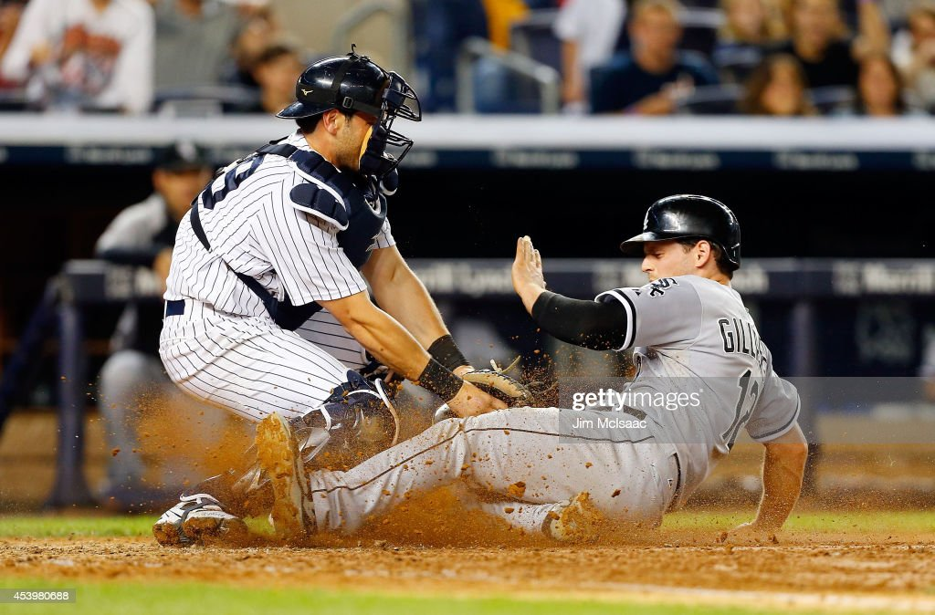 Conor Gillaspie #12 of the Chicago White Sox is tagged out at home by Francisco Cervelli #29 of the New York Yankees to end the sixth inning at Yankee Stadium on August 22, 2014 in the Bronx borough of New York City.