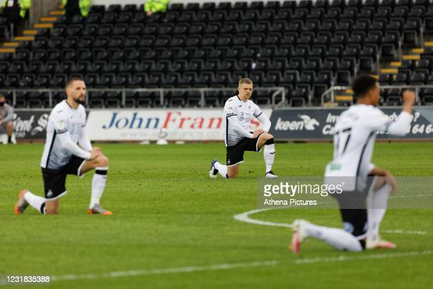 Conor Hourihane, Jake Bidwell and Morgan Whittaker of Swansea Citytake the knee prior to kick off during the Sky Bet Championship match between...