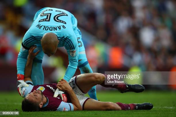 Conor Hourihane of Aston Villa goes down injured and is helped by Darren Randolph of Middlesbrough during the Sky Bet Championship Play Off Semi...