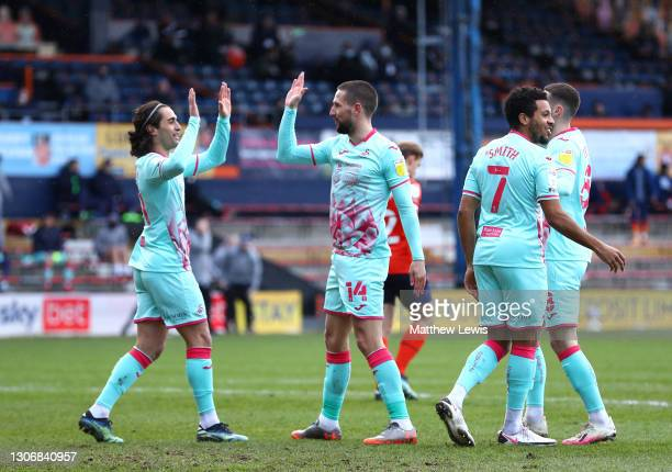 Conor Hourihane of Swansea City celebrates with teammates after scoring his team's first goal during the Sky Bet Championship match between Luton...