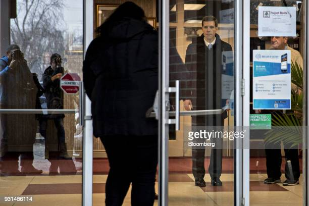 Conor Lamb Democratic candidate for the US House of Representatives center stands in the Our Lady of Victory Church polling location in Carnegie...