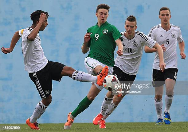 Conor Masterson of Ireland competes for the ball against Benjamin Henrichs and Max Besuschkow of Germany during the UEFA Under17 Elite Round between...