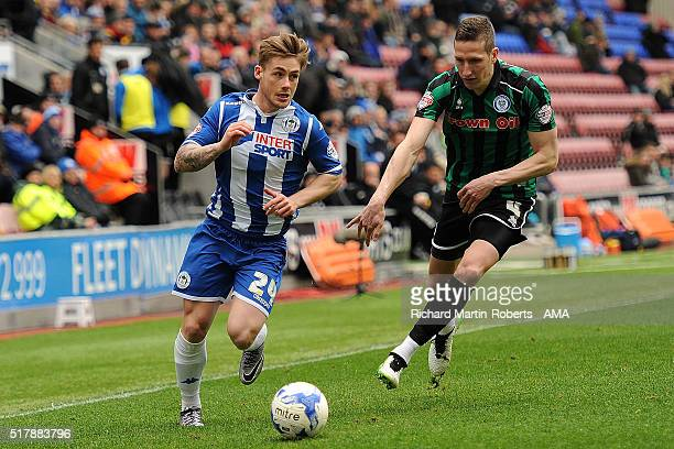 Conor McAleny of Wigan Athletic competes with Jim McNulty of Rochdale during the Sky Bet Football League One match between Wigan Athletic and...