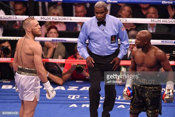 Conor McGregor and Floyd Mayweather Jr stare each other down after round one in their super welterweight boxing match at TMobile Arena on August 26...
