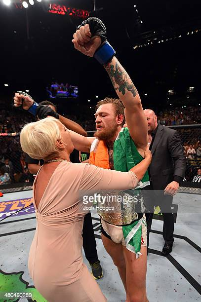 Conor McGregor celebrates with a family member after his victory over Chad Mendes in their UFC interim featherweight title fight during the UFC 189...