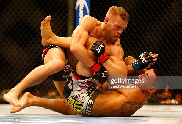 Conor McGregor elbows Max Holloway on the ground in their featherweight bout at TD Garden on August 17 2013 in Boston Massachusetts