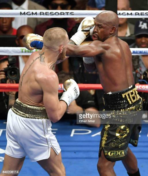 Conor McGregor hits Floyd Mayweather Jr with a left in the sixth round of their super welterweight boxing match at TMobile Arena on August 26 2017 in...