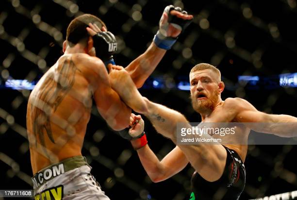 Conor McGregor kicks Max Holloway in their featherweight bout at TD Garden on August 17 2013 in Boston Massachusetts
