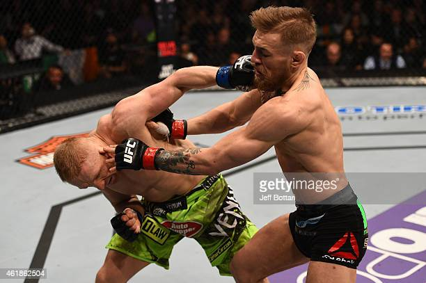 Conor McGregor of Ireland and Dennis Siver of Germany exchange punches in their featherweight fight during the UFC Fight Night event at the TD Garden...