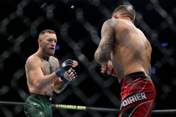 Conor McGregor of Ireland and Dustin Poirier face off in the first round in their lightweight bout during UFC 264: Poirier v McGregor 3 at T-Mobile...