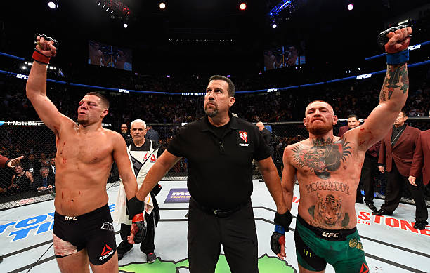 Conor McGregor of Ireland and Nate Diaz raise their hands and wait to hear the judges decision after their welterweight bout during the UFC 202 event...