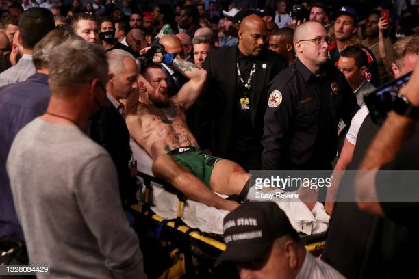 Conor McGregor of Ireland is carried out of the arena on a stretcher after injuring his ankle in the first round of his lightweight bout against...