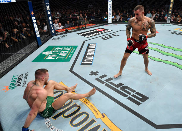 Conor McGregor of Ireland lays on the canvas after suffering an ankle injury at the end of the first round against Dustin Poirier in their...