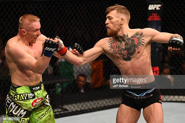 Conor McGregor of Ireland punches Dennis Siver of Germany in their featherweight fight during the UFC Fight Night event at the TD Garden on January...