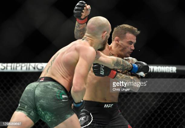 Conor McGregor of Ireland punches Dustin Poirier in a lightweight fight during the UFC 257 event inside Etihad Arena on UFC Fight Island on January...