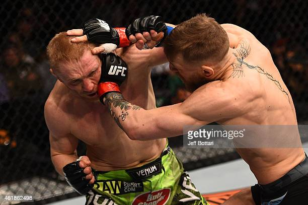 Conor McGregor of Ireland pushes Dennis Siver of Germany in their featherweight fight during the UFC Fight Night event at the TD Garden on January 18...