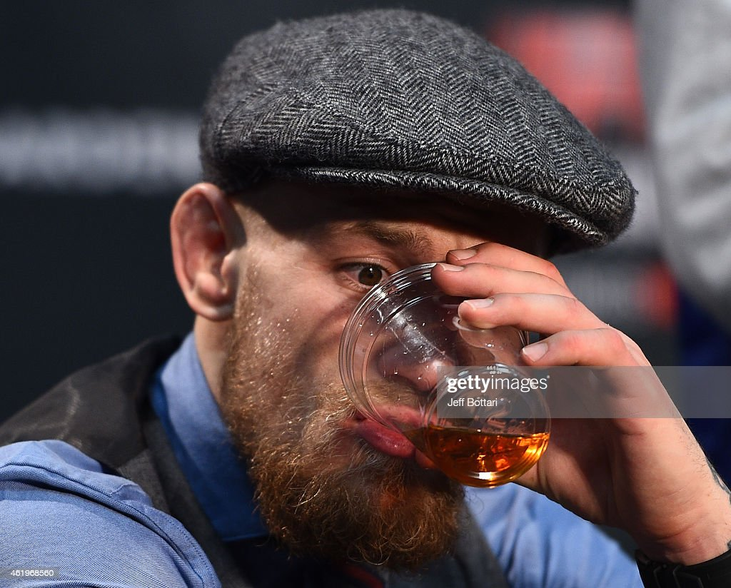 Conor McGregor of Ireland takes a drink of Irish Whiskey at the post fight press conference during the UFC Fight Night event at the TD Garden on January 18, 2015 in Boston, Massachusetts.
