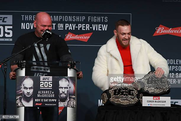 Conor McGregor of Ireland takes Eddie Alvarez's lightweight belt during the UFC 205 press conference at The Theater at Madison Square Garden on...