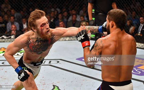 Conor McGregor punches Chad Mendes in their UFC interim featherweight title fight during the UFC 189 event inside MGM Grand Garden Arena on July 11...