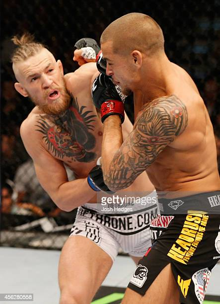 Conor McGregor punches Dustin Poirier in their featherweight fight during the UFC 178 event inside the MGM Grand Garden Arena on September 27 2014 in...
