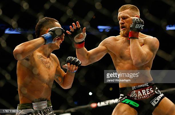 Conor McGregor punches Max Holloway in their featherweight bout at TD Garden on August 17 2013 in Boston Massachusetts