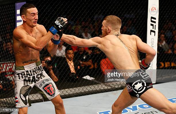 Conor McGregor punches Max Holloway in their UFC featherweight bout at TD Garden on August 17, 2013 in Boston, Massachusetts.