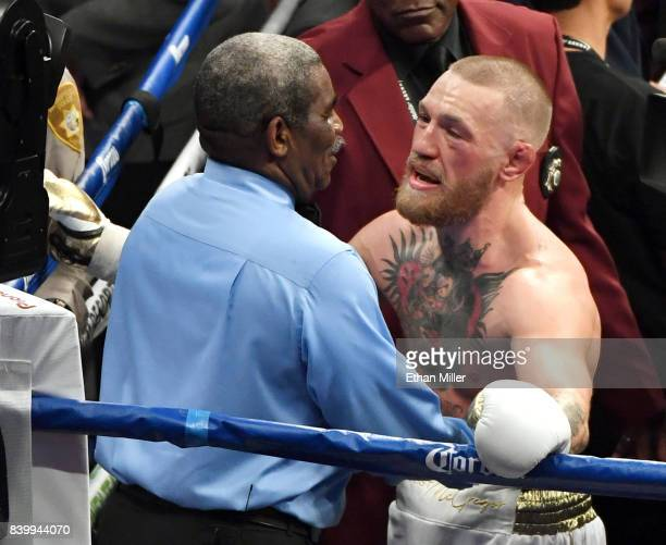 Conor McGregor talks with referee Robert Byrd after he stopped McGregor's super welterweight boxing match against Floyd Mayweather Jr giving him a...