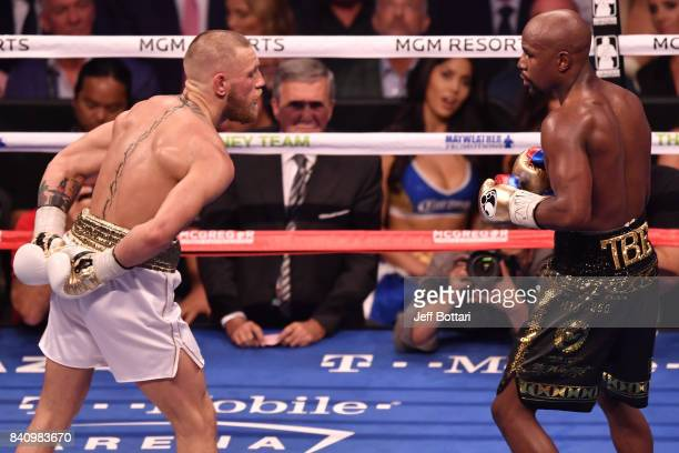 Conor McGregor taunts Floyd Mayweather Jr by holding his hands behind his back in their super welterweight boxing match at TMobile Arena on August 26...