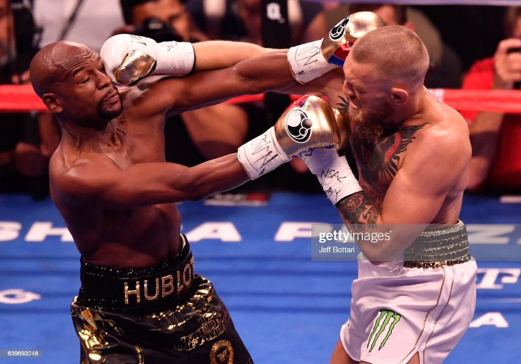 Conor McGregor throws a punch at Floyd Mayweather Jr. during their super welterweight boxing match on August 26, 2017 at T-Mobile Arena in Las Vegas, Nevada.