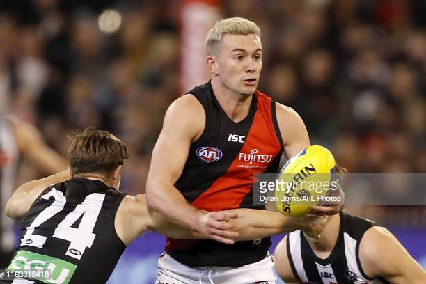 Conor McKenna of the Bombers is tackled by Josh Thomas of the Magpies during the 2019 AFL round 23 match between the Collingwood Magpies and the...