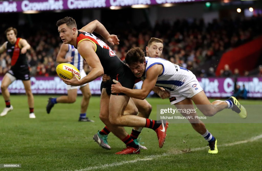 Conor McKenna of the Bombers is tackled by Nathan Hrovat of the Kangaroos during the 2018 AFL round15 match between the Essendon Bombers and the North Melbourne Kangaroos at Etihad Stadium on July 01, 2018 in Melbourne, Australia.