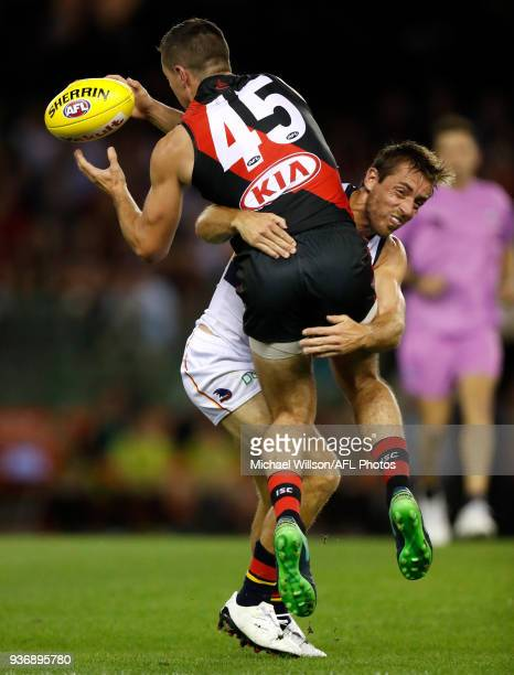 Conor McKenna of the Bombers is tackled by Richard Douglas of the Crows during the 2018 AFL round 01 match between the Essendon Bombers and the...