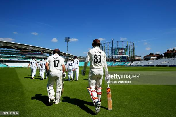 Conor McKerr of and Rory Burns of Surrey make their way out to start their innings on day three of the Specsavers County Championship Division One...