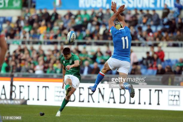 Conor Murray of Ireland takes the conversion as Angelo Esposito of Italy tries to charge him down during the Guinness Six Nations match between Italy...
