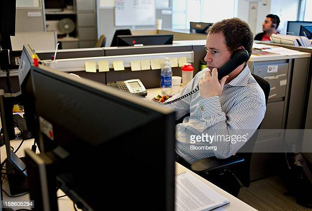 Conor Ryan a clearing operations analyst talks on the phone as he works on the clearing floor of the CME Group Inc's Chicago Board of Trade offices...