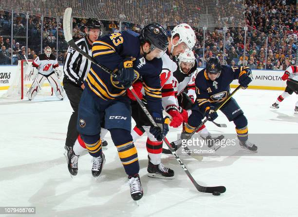 Conor Sheary and Evan Rodrigues of the Buffalo Sabres battle for the puck against Damon Severson and Kyle Palmieri of the New Jersey Devils during an...