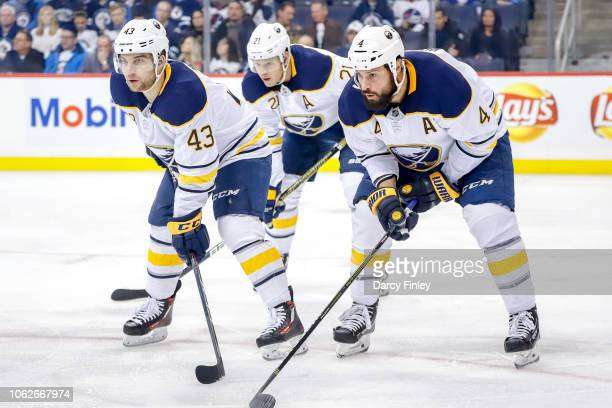 Conor Sheary Kyle Okposo and Zach Bogosian of the Buffalo Sabres get set during a first period faceoff against the Winnipeg Jets at the Bell MTS...
