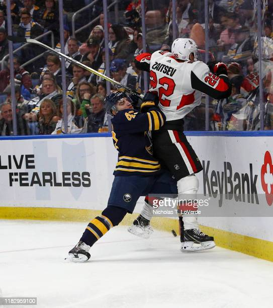 Conor Sheary of the Buffalo Sabres finishes his check on Nikita Zaitsev of the Ottawa Senators during the second period of play at KeyBank Center on...