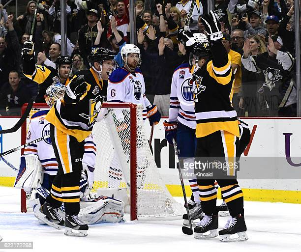Conor Sheary of the Pittsburgh Penguins celebrates with teammates after scoring the game winning goal against the Edmonton Oilers at PPG PAINTS Arena...