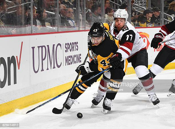 Conor Sheary of the Pittsburgh Penguins handles the puck in front of Anthony DeAngelo of the Arizona Coyotes at PPG Paints Arena on December 12 2016...