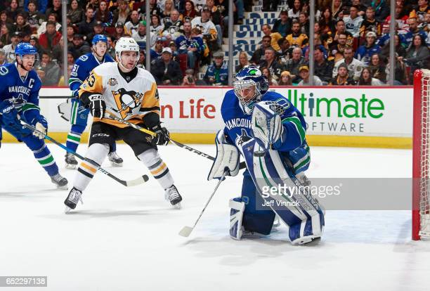 Conor Sheary of the Pittsburgh Penguins looks on as Ryan Miller of the Vancouver Canucks makes a save during their NHL game at Rogers Arena March 11,...