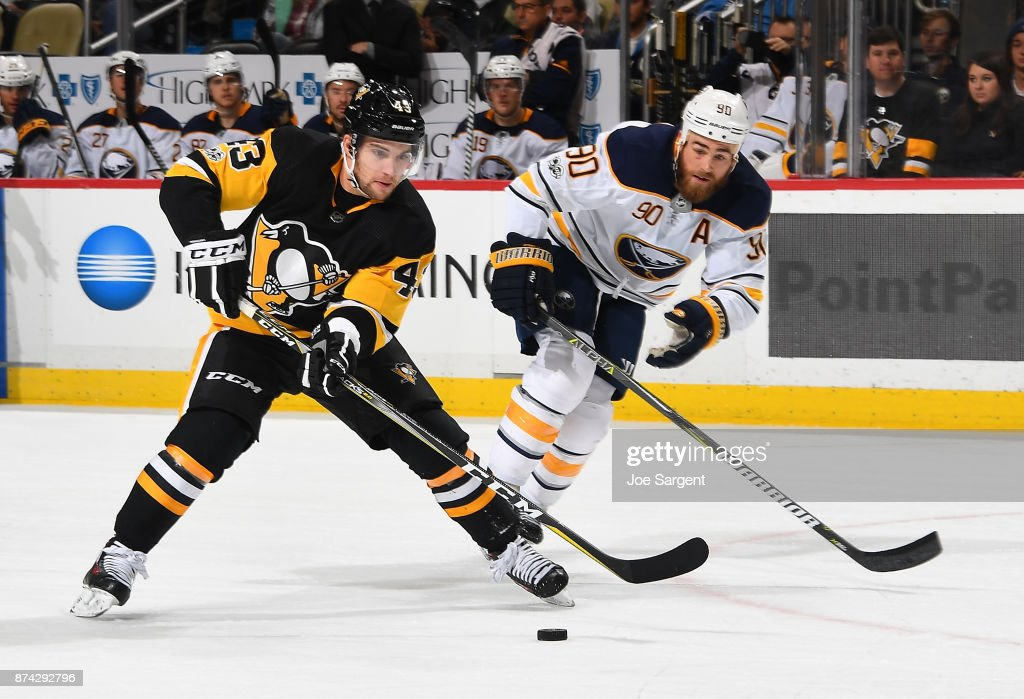 Conor Sheary #43 of the Pittsburgh Penguins moves the puck up ice in front of Ryan O'Reilly #90 of the Buffalo Sabres at PPG Paints Arena on November 14, 2017 in Pittsburgh, Pennsylvania.
