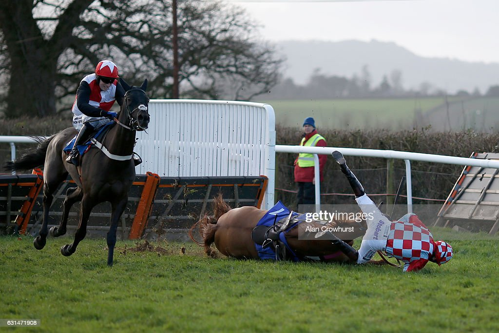 Conor Shoemark riding Forcast fall at the last when leading to leave Kieron Edgar riding Space Oddity (L) to win The Bathwick Tyres Handicap Hurdle Race at Taunton Racecourse on January 11, 2017 in Taunton, England.