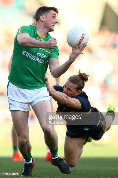 Conor Sweeney of Ireland looks to hand pass while being tackled by Nathan Fyfe of Australia during game two of the International Rules Series between...