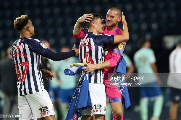Conor Townsend and Sam Johnstone of West Bromwich Albion embrace as they celebrate promotion to the Premier League on the pitch at the end of the Sky...