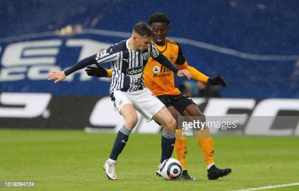 Conor Townsend of West Bromwich Albion battles for possession with Owen Otasowie of Wolverhampton Wanderers during the Premier League match between...