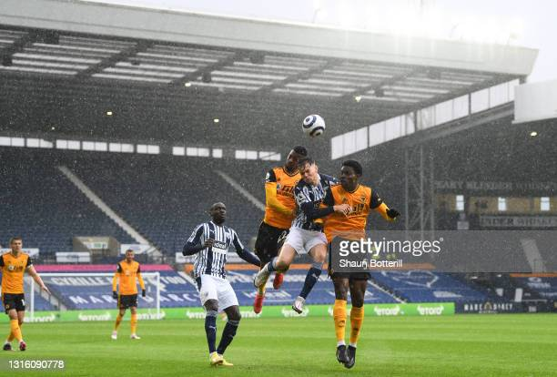 Conor Townsend of West Bromwich Albion competes for a header with Nelson Semedo and Owen Otasowie of Wolverhampton Wanderers during the Premier...